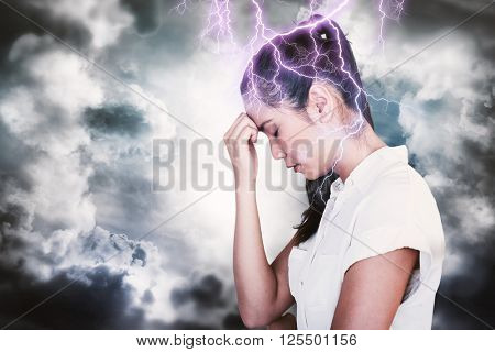 Casual upset businesswoman with head bowed against dark sky with white clouds