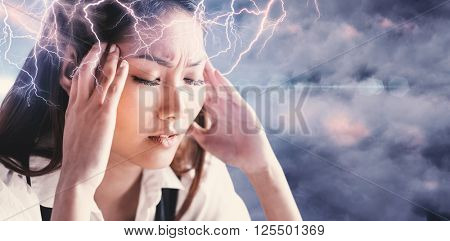 Nervous businesswoman holding her head against cloudy sky
