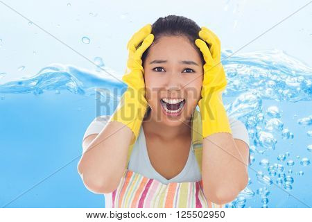 Distressed woman wearing apron and rubber gloves against close up on blue sparkling water