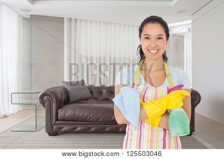 Woman standing with arms crossed holding cleaning products against brown leather couch in a modern living room
