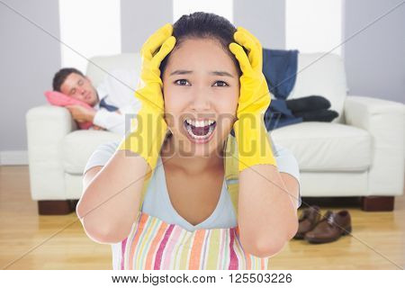 Distressed woman wearing apron and rubber gloves against calm attractive businessman lying on couch