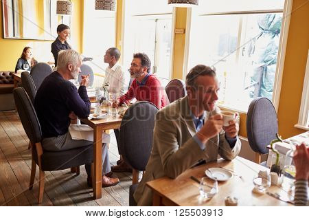 Overview of customers and a waitress in restaurant interior