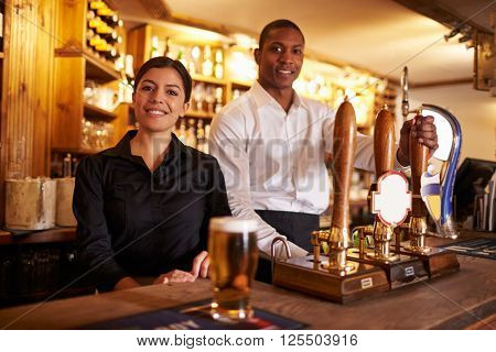 A young man and woman working behind a bar look to camera