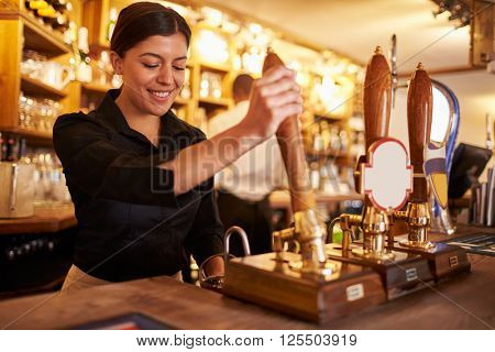 A young woman working behind a bar preparing drinks