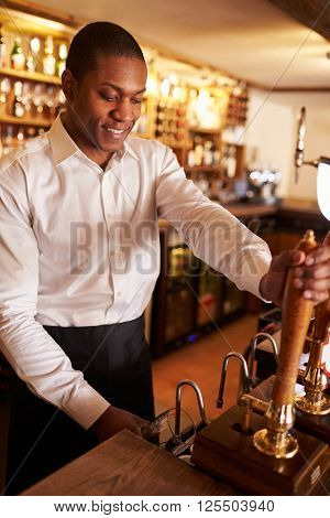A young black man working behind a bar preparing drinks