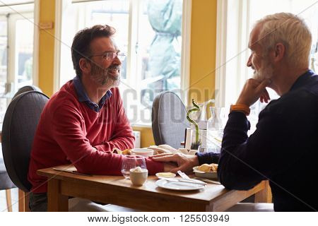 A male couple holding hands at a restaurant table, side view