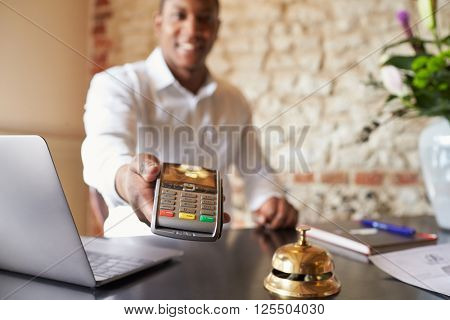 Concierge at hotel reception holds credit card reader to camera