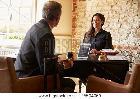 Guest talking to woman at hotel check in desk