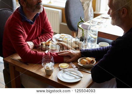Male couple hold hands at a restaurant table, elevated view