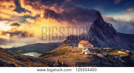 Great view of the foggy valley. Clouds covered the mystic mountain range. Dramatic scene. Location National Park Tre Cime di Lavaredo, Locatelli. Dolomites Alps, Tyrol. Italy, Europe. Beauty world.