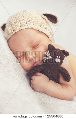 Newborn baby in knitted cap beige with brown ears and a beige knitted panties, sleeping sweetly in a light gray blanket tucked under him arms and legs and hugging a toy cat