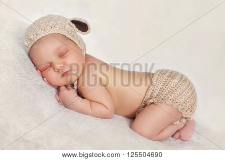 Newborn baby in knitted cap beige with brown ears and a beige knitted panties, sleeping sweetly in a light gray blanket tucked themselves under the arms and legs