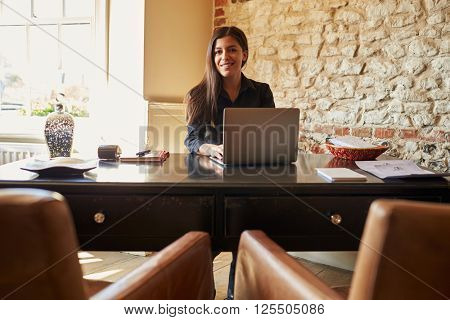 Young woman at the check-in desk of a hotel looks to camera