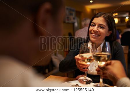 Young couple make a toast at restaurant, over-shoulder view