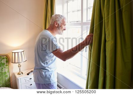 Middle aged man gets up and opens the curtains in hotel room