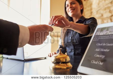 Guest takes room key card at check-in desk of hotel, close up