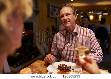 Senior couple eating meal in a restaurant, over-shoulder view