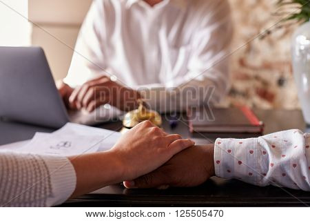 Multi ethnic couple hold hands at hotel check in desk, detail
