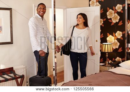 A young multi ethnic couple looking at their hotel room