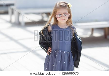 Portrait of a little girl with blond straight hair,big sun glasses,wearing a leather jacket of black color and gray-blue gown,in her hair wears a white flower in the city posing outdoors in the spring