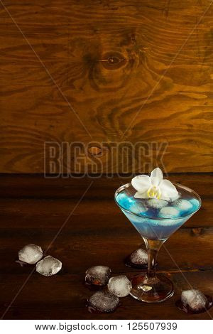 Blue cocktail in a martini glass with white orchid vertical copy space. Blue Martini. Blue curacao liqueur. Blue margarita. Blue Hawaiian cocktail
