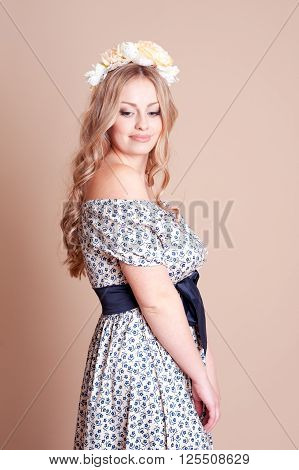 Beautiful young blonde girl 20-22 year old posing over beige. Wearing hairband with flowers. Elegance.