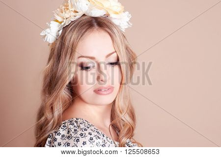 Beautiful young blonde girl 20-22 year old posing over beige. Wearing hairband with flowers. Closeup portrait. Elegance.