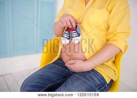 Beautiful pregnant woman looking at camera and smiling sitting on a couch. The happiest time for every woman. Socks in the hands of a pregnant woman on her belly.