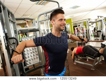 Handsome sporty young man training on weight machine in gym.