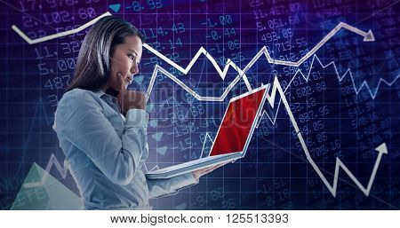 Businesswoman with finger on cheek using laptop against stocks and shares