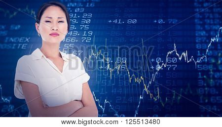 Business colleagues with arms crossed in office against stocks and shares
