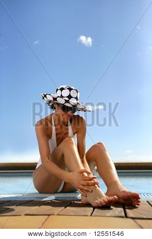 Portrait of a young woman in swimsuit sitting at a poolside