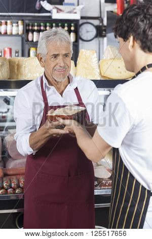 Salesman Receiving Cheese From Colleague In Grocery Shop