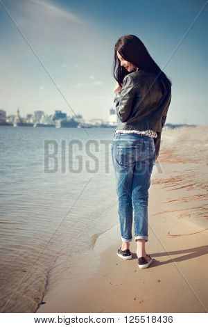 Portrait of brunette girl in casual clothes walks by the river. Sensual attractive woman relaxing on the beach and enjoying a warm sunny day.