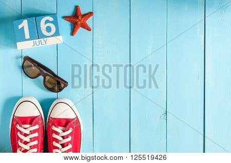 July 16th. Image of july 16 wooden color calendar on blue background. Summer day. Empty space for text.