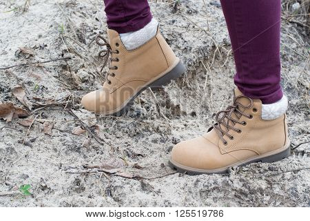 female feet shod in brown shoes standing on sand in the forest