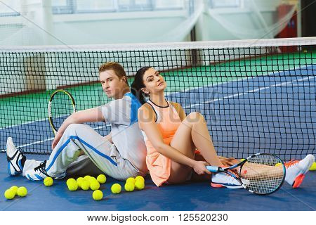 two tennis player relaxing next to a net.