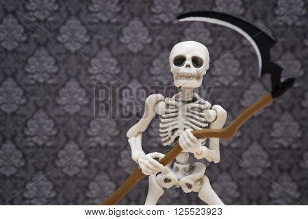 a skeleton holding a scythe of grim reaper
