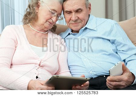 Elderly people. Elderly couple holding laptop smartphone and make purchases over the Internet in the cozy living room of the house. Elderly people communicate fun close up.