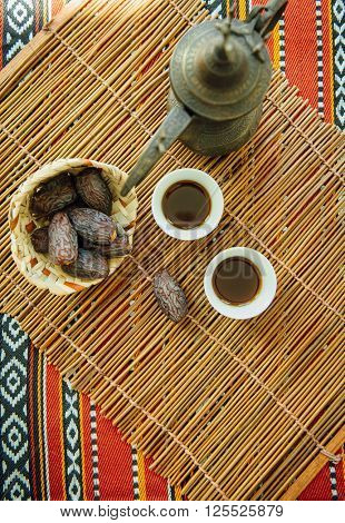 Arabic black coffee and dates. Typical middle eastern beverage and fruit offered to the guests.