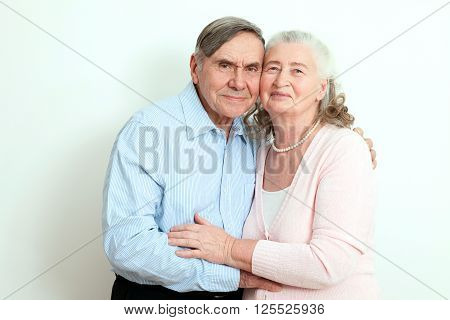 Portrait of candid senior couple enjoying their retirement. Affectionate elderly couple with beautiful beaming friendly smiles posing together in close embrace isolaned on white background