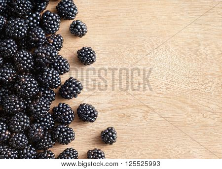 Blackberries on wooden background. Close up top view high resolution product. Harvest Concept