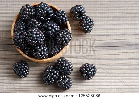 Deluxe blackberries in bowl on wooden background. Close up top view high resolution product. Harvest Concept