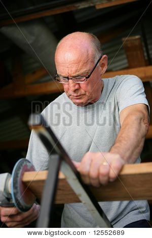 Portrait of a senior man sanding a board