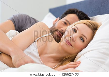 Young adult couple waking up on the bed in bedroom. Young man embracing woman while lying in bed. Happy smiling couple wake up and looking at camera. Portrait of happy woman in bed.