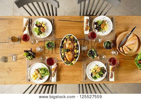 Top view of two roasted chicken in a bowl on lunch table. High angle view of dining table with salad and red wine.