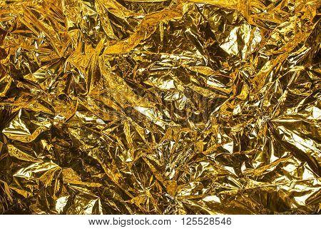 Close up wrinkled golden luminosity foil background