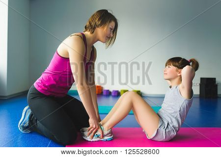 Instructor or Mother with daughter doing gymnastic exercises.