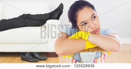 Troubled woman leaning on a mop against low section of businessman resting on sofa in living room