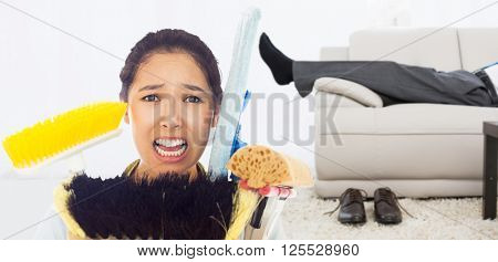 Very stressed woman with cleaning tools against low section of a businessman resting on sofa in living room